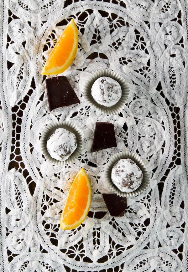 Vegan orange chocolate truffles on white lace background
