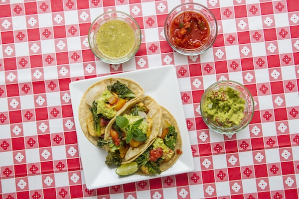 Vegan tacos with kale, guacamole, salsa, and salsa verde, on a red and white checkered table covering