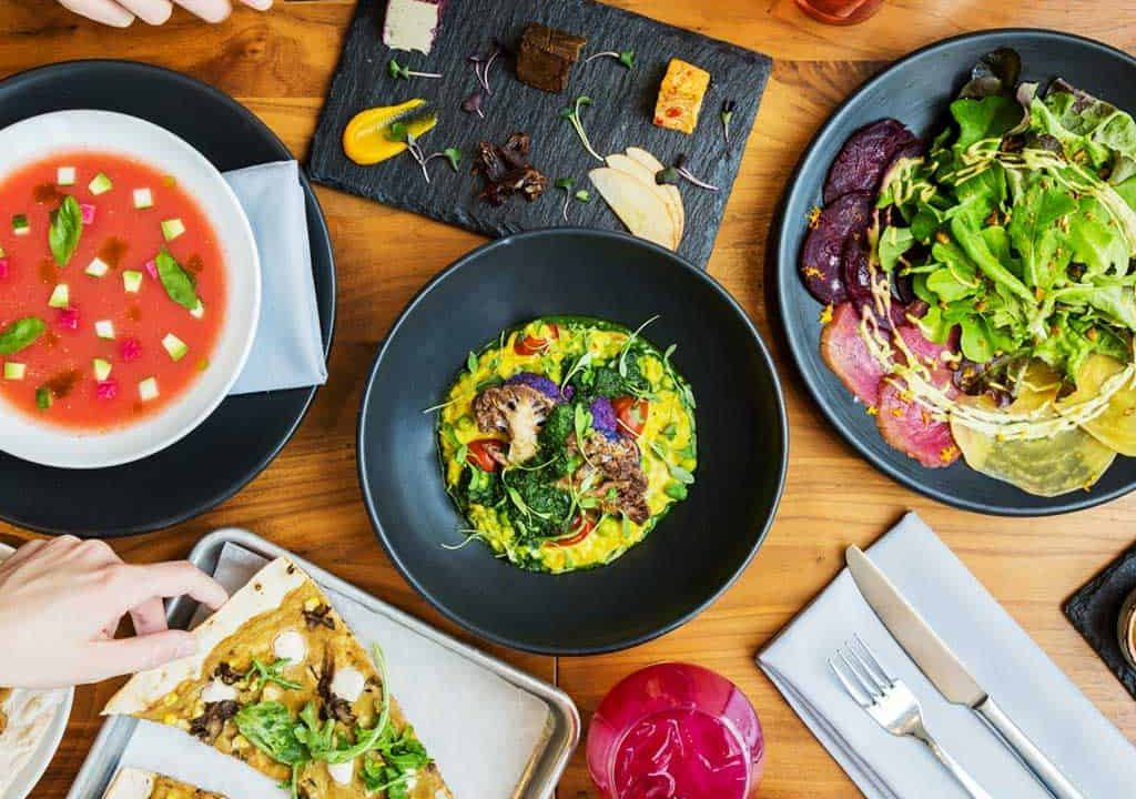 Plates of colorful vegan food on table with hands reaching for plates